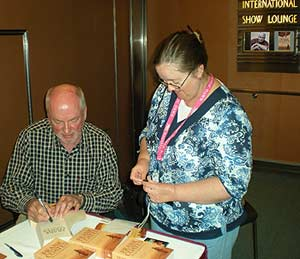Frank signs copies of The Last Maasai Warrior after his lecture attended by around two hundred readers on board the Pacific Dawn
